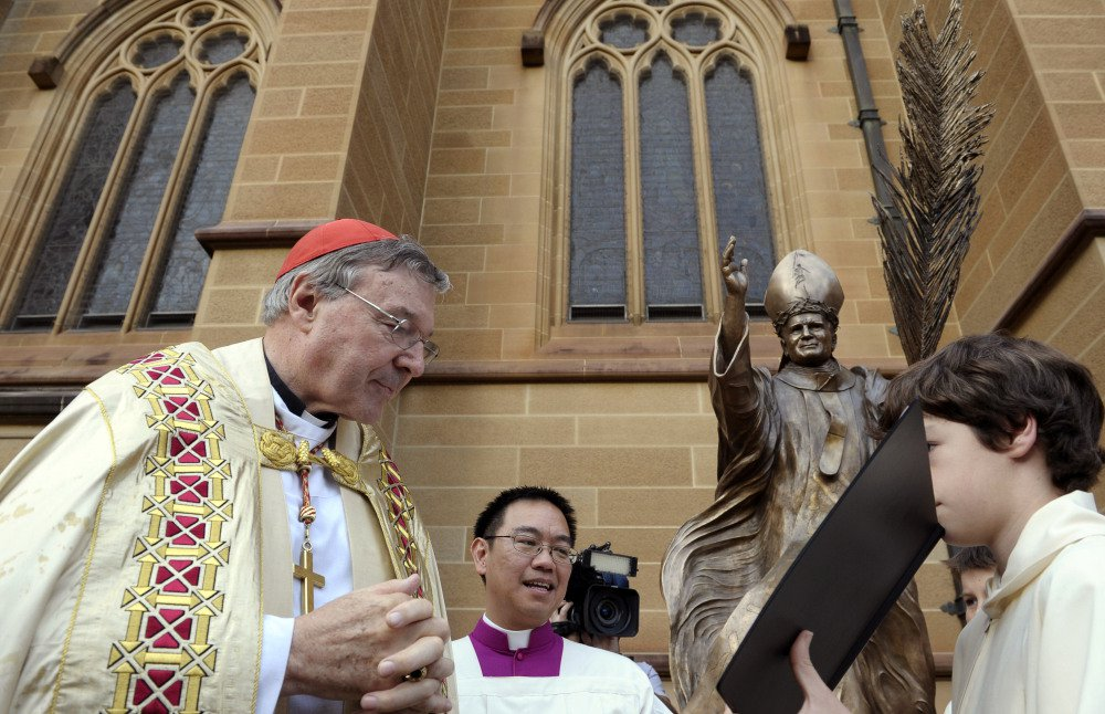 """Cardinal George Pell, left, reads a Bible during the blessing of a statue of John Paul II at St Mary's Cathedral in Sydney, Australia, in 2011. Pell faces multiple charges of """"historical sexual assault offenses,"""" meaning offenses that generally occurred in the past."""