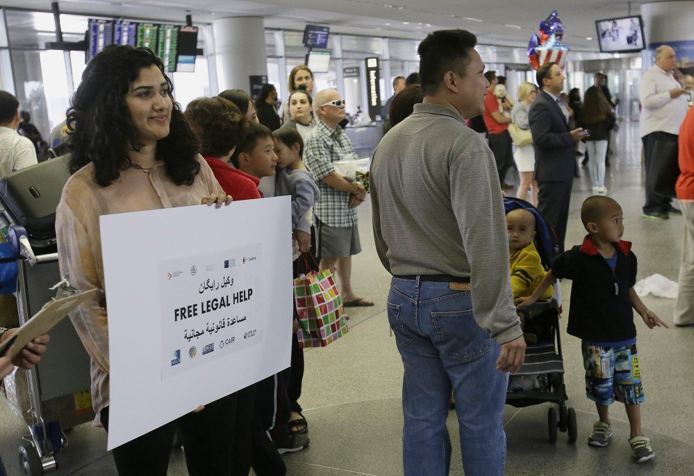 Sacha Maniar, program coordinator of the Asian Law Caucus, holds up a sign offering free legal help at the international terminal at San Francisco International Airport on Thursday. A scaled-back version of President Trump's travel ban took effect Thursday evening, stripped of provisions that brought protests and chaos at airports worldwide in January