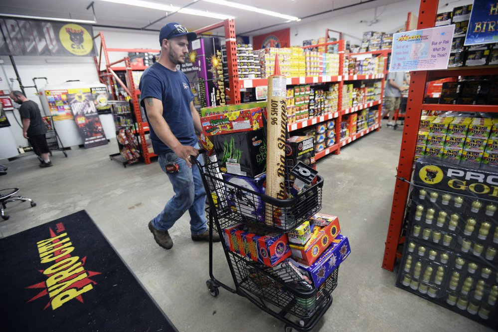 Tom Craves of Windham pushes a cart full of fireworks while shopping at Pyro City Fireworks in Windham on Friday.