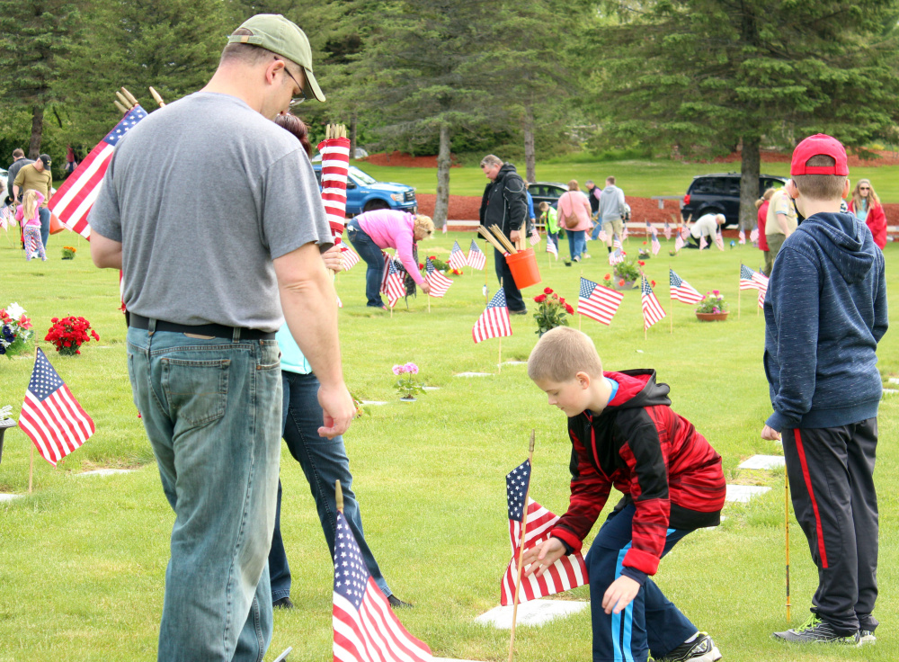 Derek Fennell, a Marine Veteran, with sons Kamren, center, and Evan placed flags Saturday at the VA Cemetery in Augusta in honor of those who have served our country.