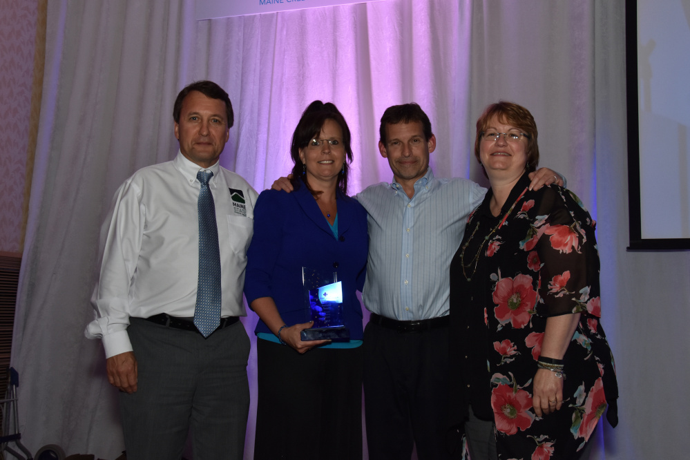 Stacey Dow, executive assistant at Maine State Credit Union, holds the Diane L. Oceretko People Helping People Award she received recently during the Maine Credit Union League's annual awards dinner. From left are Maine State CU's Tucker Cole, president and CEO; Dow; Mark Young, senior vice president and chief operating officer; and Angela Harvey, director of human resources.