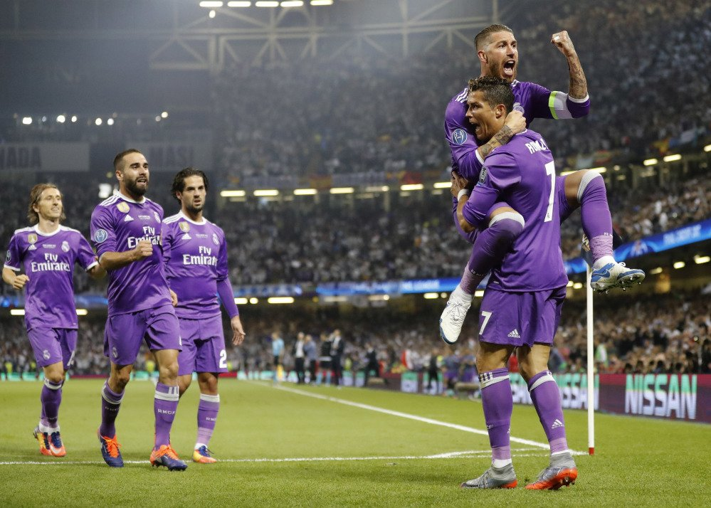 Real Madrid's Cristiano Ronaldo celebrates with Sergio Ramos, top, after scoring the opening goal during the Champions League final soccer match against Juventus Saturday at the Millennium stadium in Cardiff, Wales.