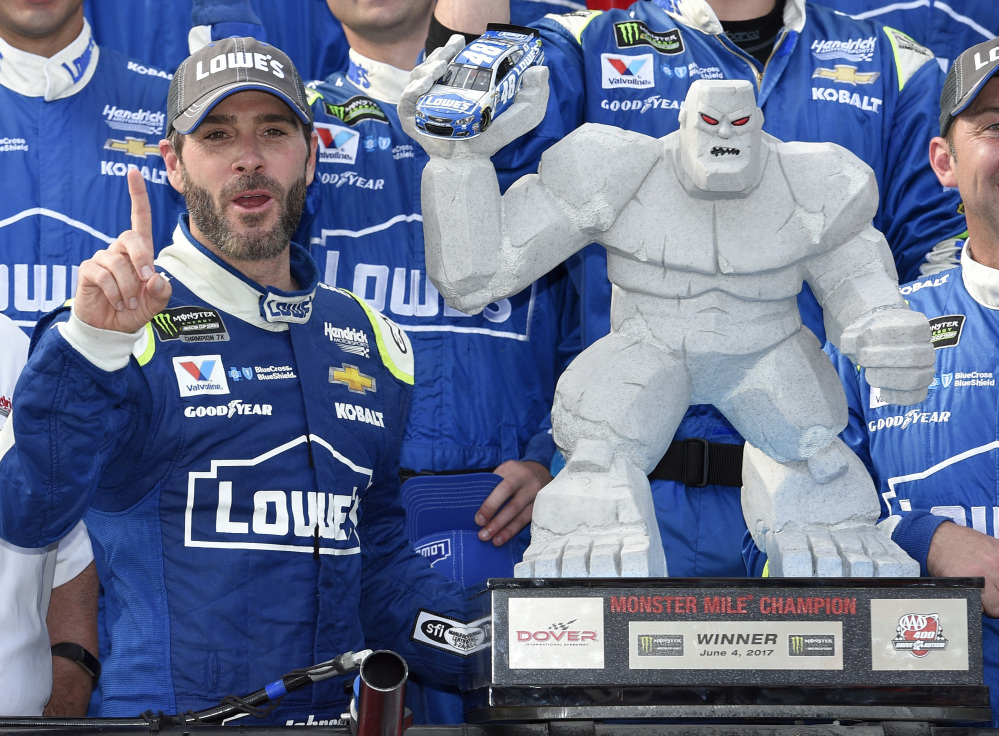 Jimmie Johnson, left, poses with the trophy in Victory Lane after he won a NASCAR Cup series race Sunday at Dover International Speedway.