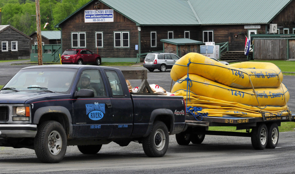 A North Country Rivers employee hauls a trailer full of white water rafts while leaving the base lodge of the company in Bingham on Monday. The Maine Warden Service continues to investigate the death of Richard Sanders last Saturday after the raft he was in flipped over on the Dead River.