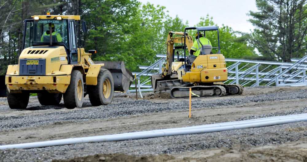 Workers use heavy equipment to bury electrical conduit at the new solar facility under construction near the Waterville campus of Colby College on Monday.