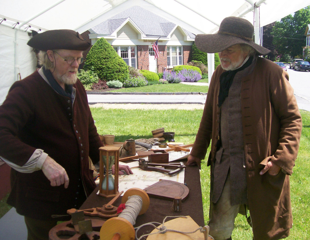 Jeff Miller, left, and Paul Daiute discuss maps, charts and navigational instruments used during the Colonial Era.