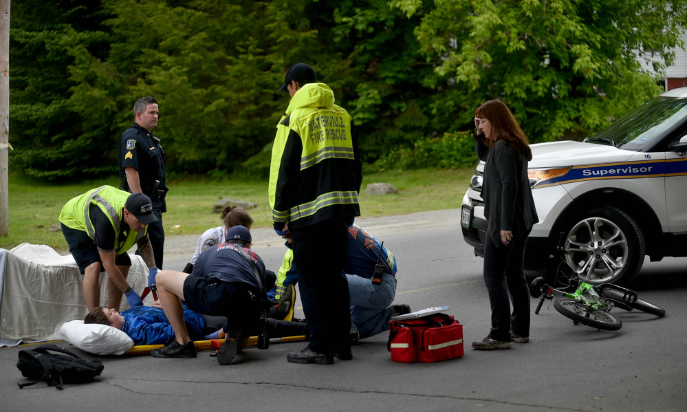 Paramedics from the Waterville Fire Department treat a boy who struck a car while riding his bicycle Tuesday on Western Avenue in Waterville.