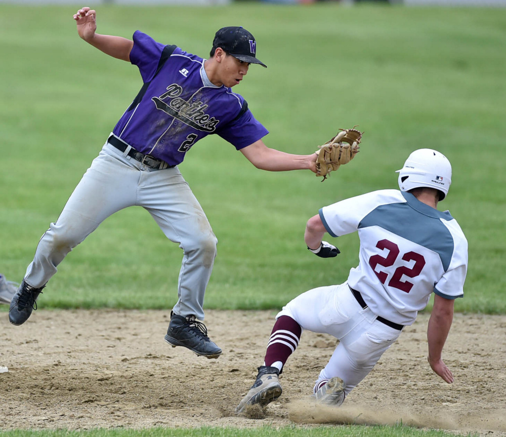 Waterville's Chay Phelps, left, leaps for the high throw to tag out Foxcroft runner Billy Brock during a Class B North prelim game Tuesday.