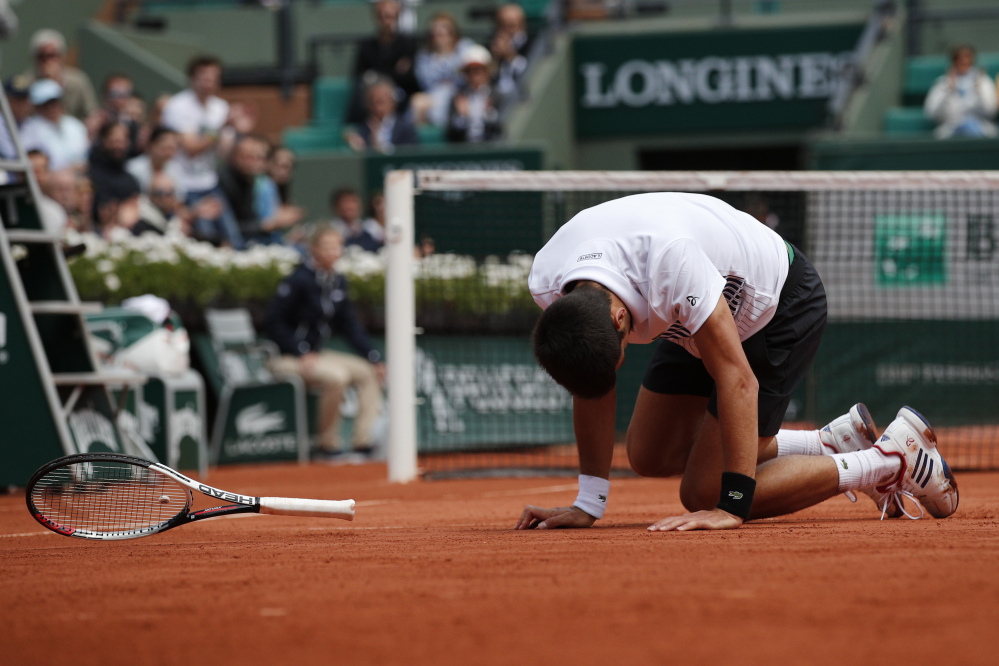 Novak Djokovic falls during his French Open quarterfinal match against Dominic Thiem on Wednesday at the Roland Garros stadium in Paris.