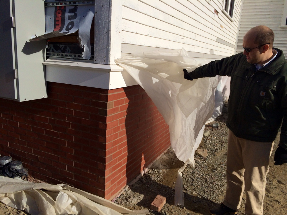 Matt Tremblay, manager of the Unity Food Hub, shows new brick siding on the former Unity Grammar School in January 2015. Renovation to convert the old school into a food hub was funded in part by federal grants.