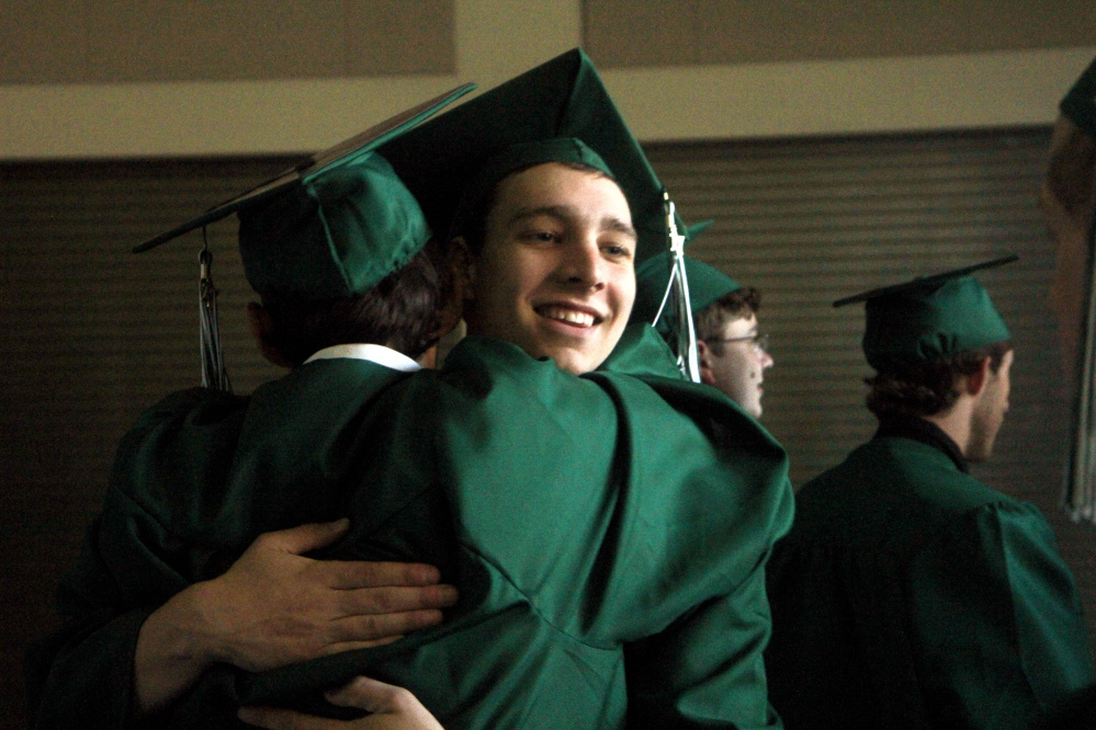 Winthrop High School senior Nickk Child hugs a classmate prior to commencement exercises on Sunday.