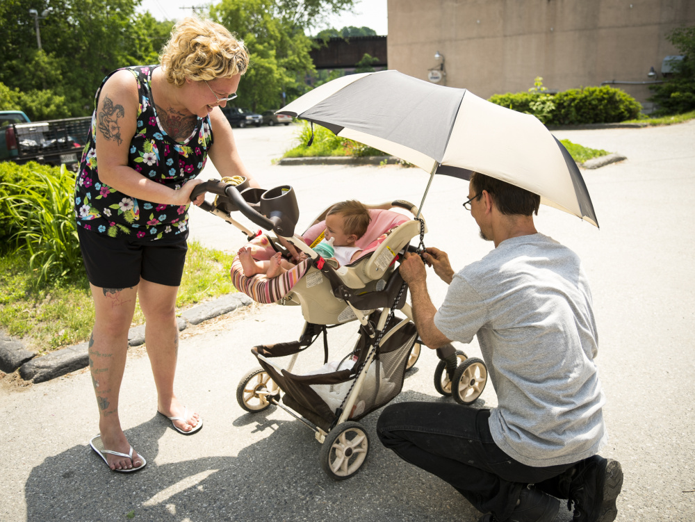 Parents Nicole and Joe Carter, of Augusta, adjust an umbrella and stroller in an effort to keep their 8 month old daughter, Persephone, shaded and cool as they walk down Water Street in Augusta on Monday.