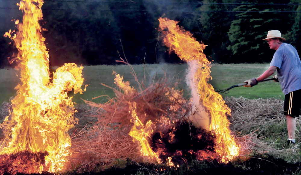 Peter Clifford throws a pitchfork full of burning brush to ignite another pile while he and his father Roger burned a field in Benton on Monday August 25, 2014.