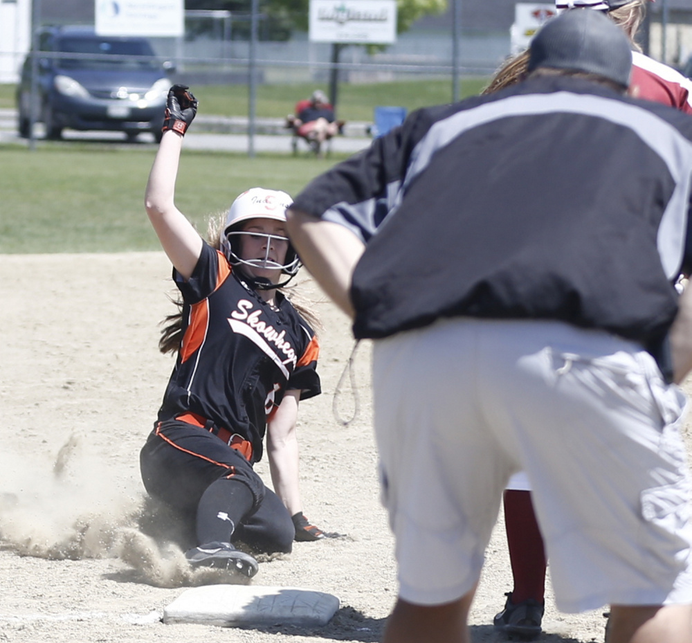 Skowhegan runner Sydney Ames slides safely into third base as coach Lee Johnson looks on during an A North semifinal game against Bangor on Saturday. The Indians will play Oxford Hills in the regional final.