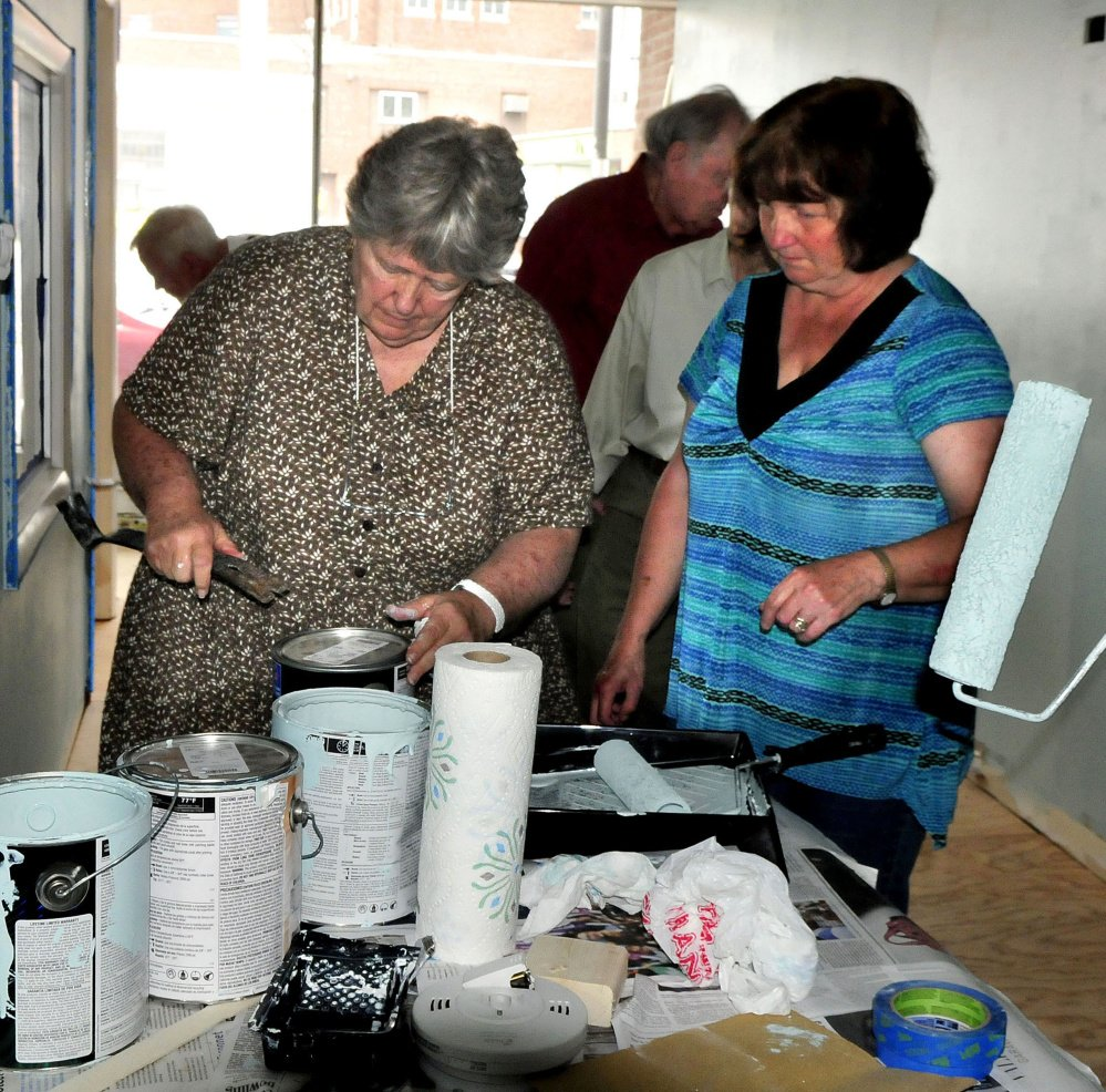 REM Co-executive Director Faye Nicholson, left, opens cans of paint for volunteers painting the new REM offices Tuesday on Temple Street in Waterville.