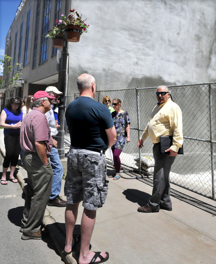 Paul Ureneck, right, leads a group of people Wednesday on a downtown Waterville tour of various ongoing revitalization projects, including the former Levine's store.
