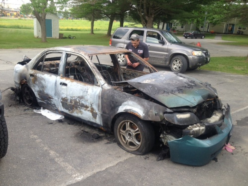 Quincy McLaughlin, of Family Circle in Skowhegan, looks over his 2001 Mazda Protege, which was consumed by fire early Monday. A 15-year-old boy has been charged with arson in connection with the setting of four car fires Monday morning in Skowhegan.