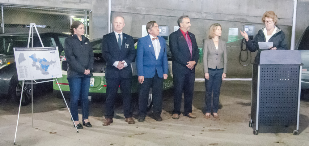 Sara Burns, president and chief executive officer of Central Maine Power Co., right, speaks at the electric car charger ribbon-cutting event Friday in the State House parking garage in Augusta.