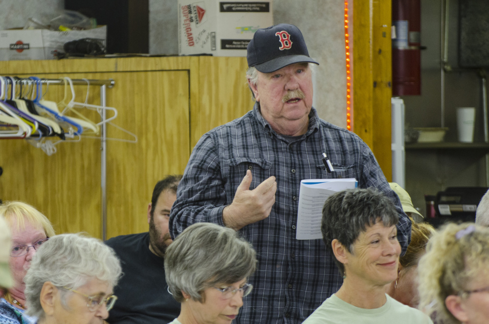 Litchfield voters show their approval of a motion on the floor Saturday during Town Meeting, held at the Sportsman's Club in Litchfield.