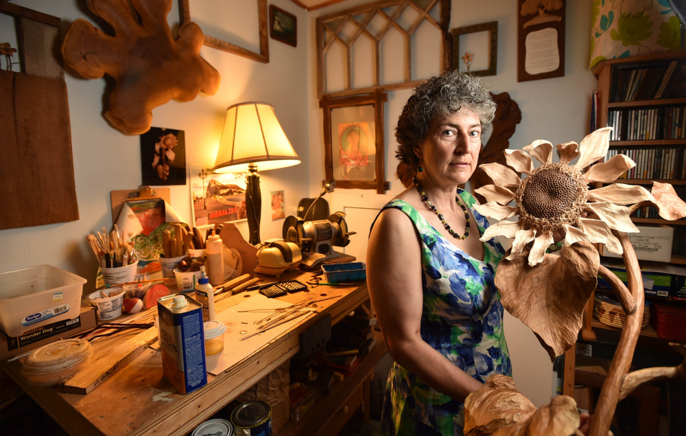 Laurie Sproul poses for a portrait with her sunflower wood sculpture in her studio at her home in Canton on Friday. Sproul is one of two Maine artists working to create a visual language for the Citizens' Climate Lobby.