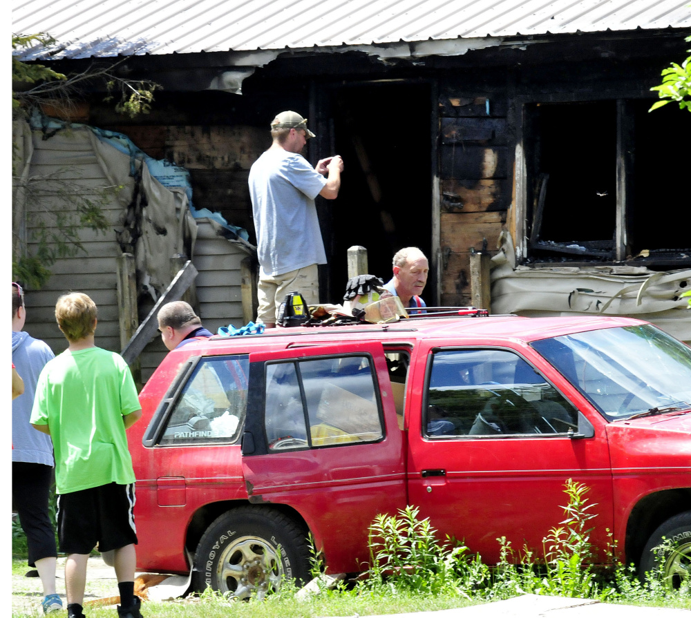Homeowner Tyler Bishop photographs the damage after fire destroyed his home Thursday on Higgins Road in Pittsfield. Firefighters from several area departments battled the fire.