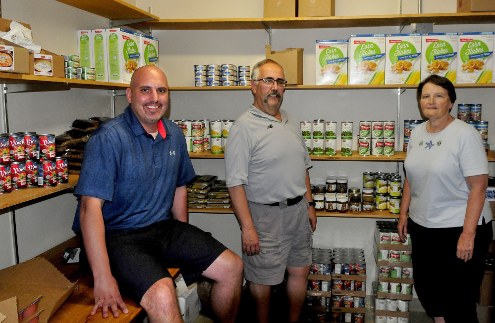 SAD 59 staff members and volunteer members of the Central Food Pantry in Madison Junior High School stand inside the stocked pantry Thursday. From left are Ryan Arnold, Al Veneziano and Doris Lindblom.