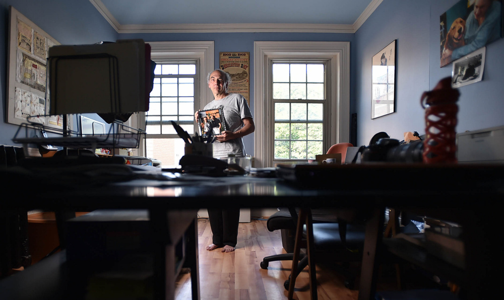 Maine International Film Festival programmer Ken Eisen poses Friday with a portrait of him and director Jonathan Demme in his MIFF office on Main Street in Waterville. Demme will be honored at the 20th annual Maine International Film Festival.