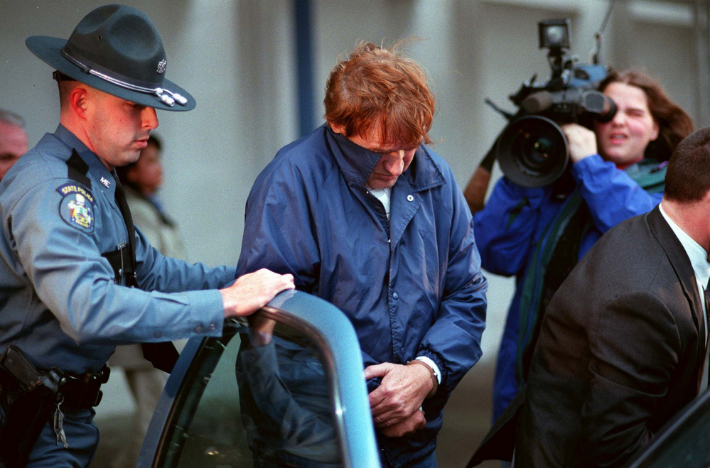 Albert Cochran is escorted by Maine State Police on March 21, 1998, to a waiting police cruiser at Portland International Jetport. Cochran returned to Maine from Florida to face murder charges in the death of Janet Baxter, of Oakland, in 1976.
