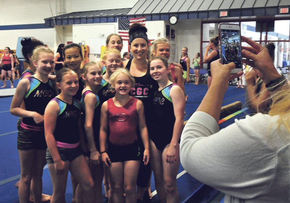 Olympic gold medalist Carly Patterson is surrounded by young area gymnasts as Kristen Starbird photographs the group during training Thursday at the Alfond Youth Center in Waterville.