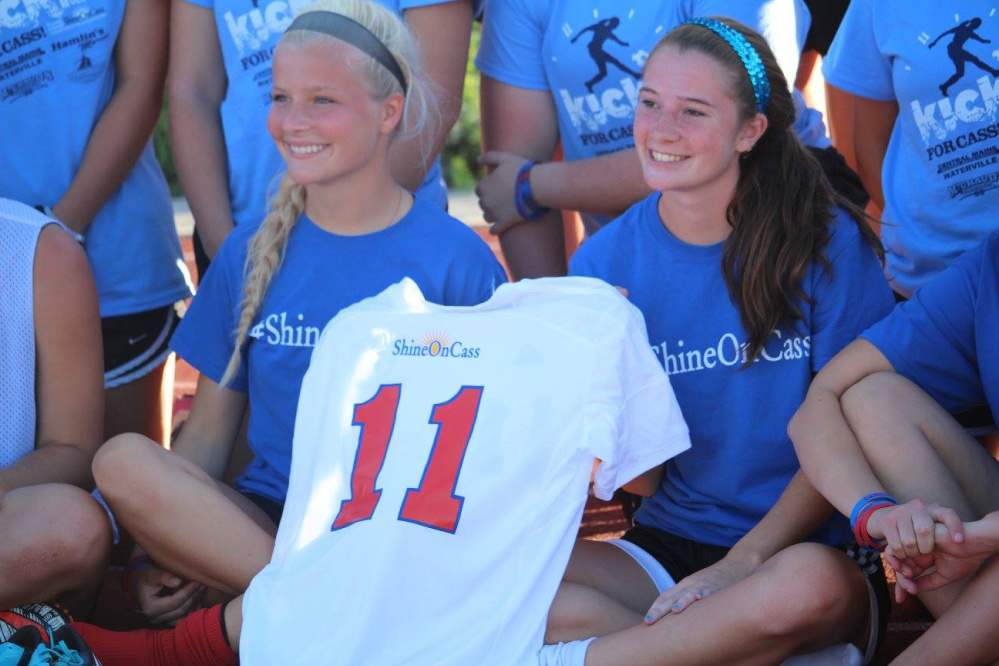 "Katie Mercier, left, and Madisyn Charest, former Messalonskee Girls Soccer players, carry Cassidy Charette's jersey at last year's 11-hour soccer event ""Kick Around the Clock for Cass."" The second annual event is planned from 9 a.m. to 8 p.m. Sunday, July 16, at Thomas College."