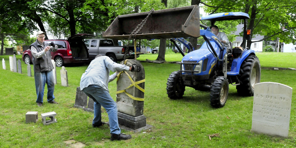 The headstone of Samuel and Sally Jewett is re-erected Tuesday at their grave in the churchyard at the former site of St. Anne's Church in Gardiner. Taking photos at left is Bill King as Hank McIntyre sets the stone while Logan Johnston lowers it from his tractor.