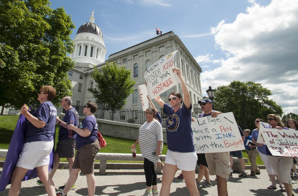 State employee union members, employees and supporters march past the State House on Monday as they protest day three of a state shutdown in Augusta.