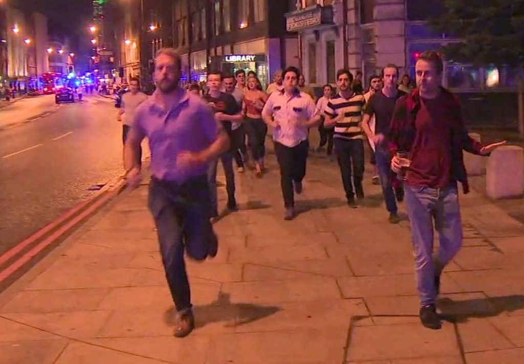 In this image taken from video footage, people run from the scene of attack, alongside a man strolling holding a pint of beer, right. People in the U.K. have responded to the deadly London Bridge attack with sorrow and distinctly British humor, hailing the man with the pint as a tongue-in-cheek symbol of defiance.
