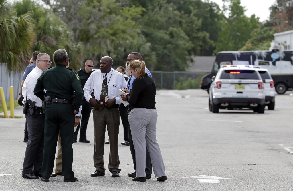 Authorities confer near the scene of a fatal shooting in an industrial area near Orlando, Fla., on Monday.