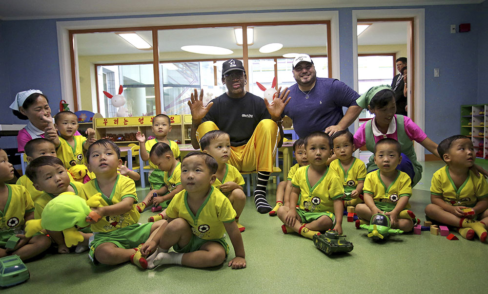 Former NBA basketball star Dennis Rodman sits with children from the Pyongyang orphanage and nursery that he visited Thursday.