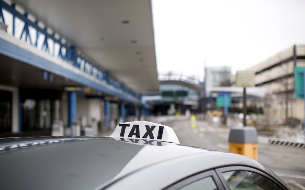 "The growing popularity of doing work on the side using the digital ""platform economy"" has helped Uber hire 1 million drivers, and the local ones compete with taxi cab companies for fares outside the Portland International Jetport, above."