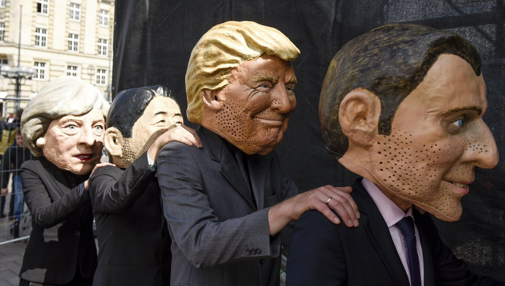 Critics of the G20 Summit stand on stage in Hamburg, Germany, wearing masks depicting, from left: British Prime Minister Theresa May, Japan Prime Minister Shinzo Abe, President Trump and French President Emmanuel Macron.