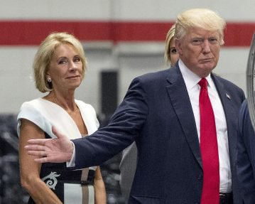 FILE - In this June 13, 2017, file photo, President Donald Trump, accompanied by Education Secretary Betsy DeVos, left, waves to members of the media as he takes a tour of Waukesha County Technical College in Pewaukee, Wis. Democratic attorneys general in 18 states and the District of Columbia are suing Education Secretary Betsy DeVos over her decision to suspend rules meant to protect students from abuses by for-profit colleges. The lawsuit was filed Thursday, July 6, 2017,  in federal court in Washington and demands implementation of borrower defense to repayment rules. (AP Photo/Andrew Harnik, File)