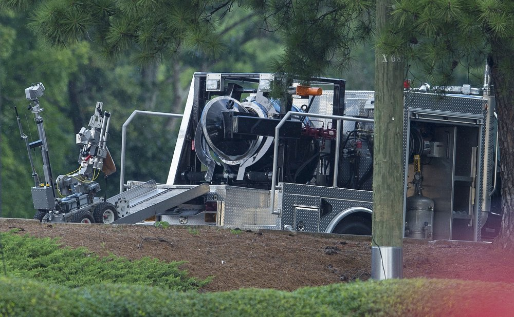 A police robot carries a device into a bomb squad vehicle in Marietta on Friday. A man who claimed to have a bomb forced a standoff until he was killed in an officer involved shooting.