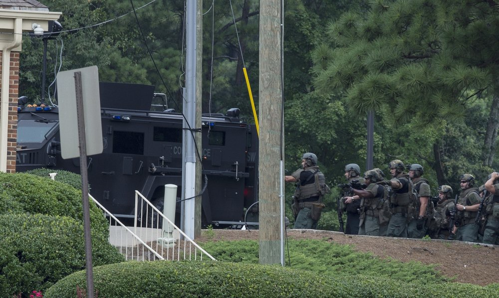 "Police officers move toward a Wells Fargo Bank on Friday in Marietta, Georgia. A man who claimed to have a bomb that could ""take out the room"" barricaded himself inside the suburban Atlanta bank Friday, sparking an hours-long standoff that forced police to bust through a brick wall of the building and later ended with the suspect's death."