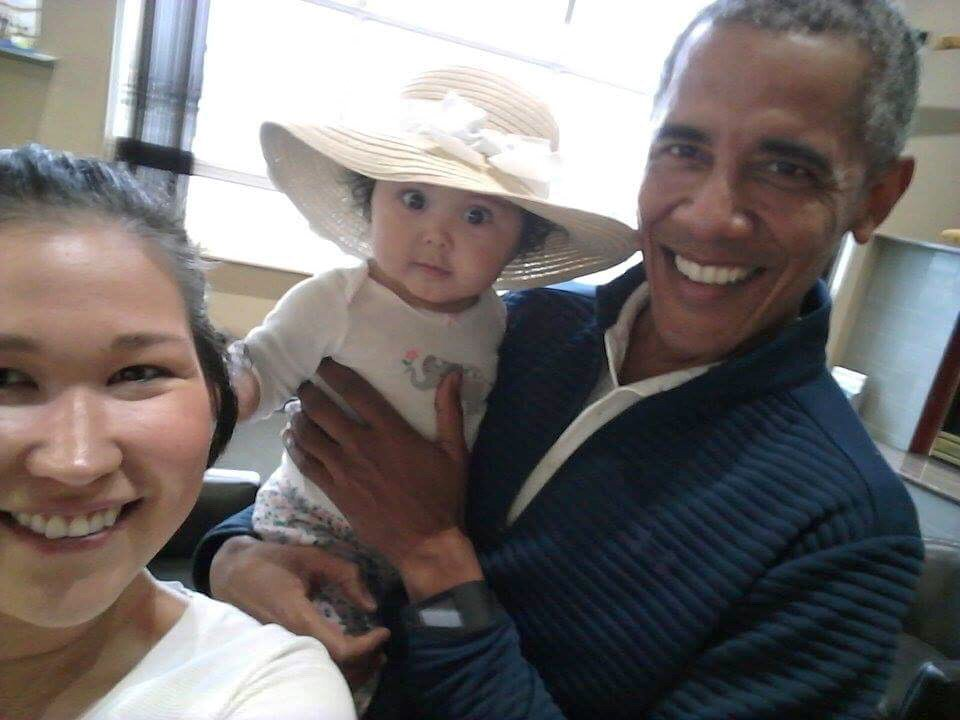 "In this photo provided by Jolene Jackinsky, former President Barack Obama holds Jackinsky's 6-month-old baby girl while posing for a selfie with the pair at a waiting area at Anchorage International Airport in Alaska. Jackinsky said Obama walked up to her and asked, ""Who is this pretty girl?"""