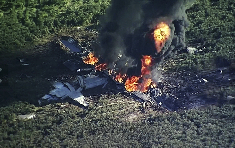 Smoke and flames rise from the military plane that crashed in a farm field, in  Mississippi, killing 16 people.
