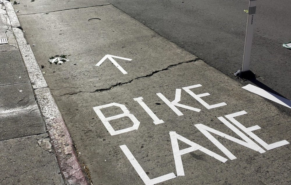A sign made by activists with tape separates cyclists from traffic on a San Francisco street.