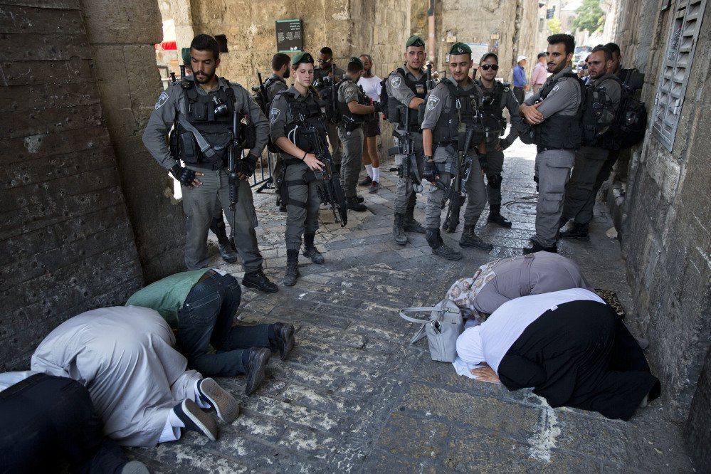 Palestinian Muslims pray in protest as Israeli police stand guard in Jerusalem on Tuesday. The protestors contested Israel's installation of a metal detector at a holy site.