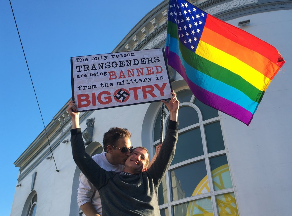 Nick Rondoletto, left, and Doug Thorogood, a couple from San Francisco, wave a rainbow flag and hold a sign against a proposed ban of transgendered people in the military at a protest in the Castro District in San Francisco. Demonstrators flocked to a plaza named for San Francisco gay-rights icon Harvey Milk to protest President Trump's abrupt ban on transgender troops in the military.