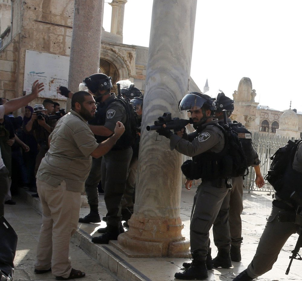 An Israeli police officer aims his gun at Palestinians during clashes Thursday at the Al-Aqsa Mosque compound  in Jerusalem's Old City. Mass protests are expected for Friday prayers, the highlight of the Muslim religious week.