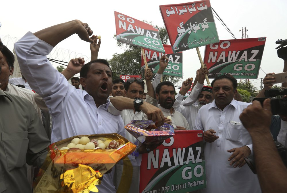 Supporters of opposition parties share sweets to celebrate the dismissal of Pakistani Prime Minister Nawaz Sharif in Peshawar on Friday.