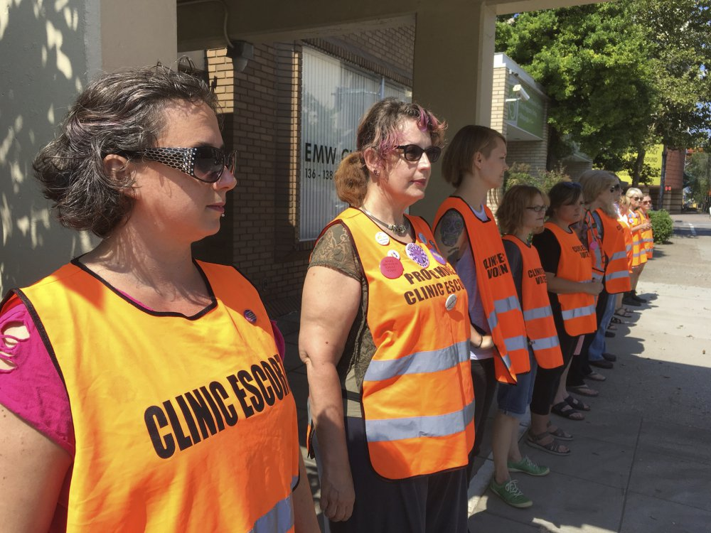 Escort volunteers line up outside the EMW Women's Surgical Center in Louisville, Ky.