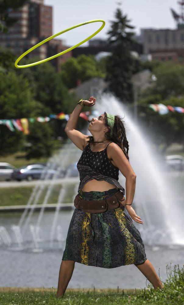Hoop dancer Grace Raggiani grooves to loud salsa music during the 15th annual Festival of Nations. Raggiani said she dances at the park almost every day, but the music from the festival was a welcome addition to her routine. Staff photo by Ben McCanna