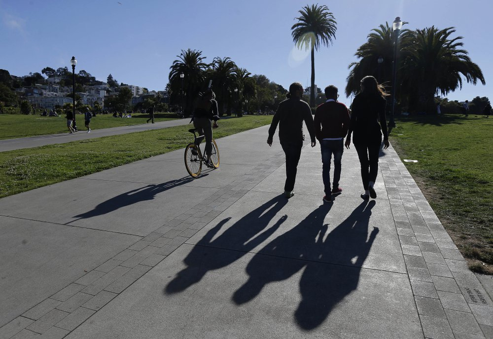 Mike Gougherty and Julie Rajagopal walk with their 16-year-old foster son from Eritrea at Dolores Park in San Francisco. She stayed up through the night calling government workers and charity officials in Cairo to speed the paperwork.